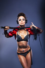 stock photo of scourge  - Sexy fetish woman dj in lingerie holding whip with headphones listening to the music - JPG