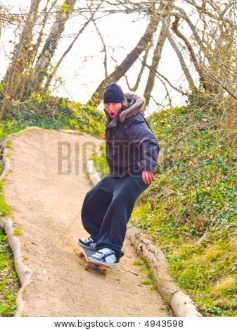 Guy On His Skateboard Flying Down A Path