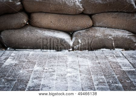 Old Brown Sandbags On Snow Covered Wooden Floor