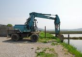 pic of jcb  - A blue engineering vehicle by the side of an area of salt flats in Slovenia - JPG