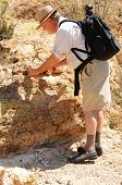 foto of paleontologist  - Senior geologist tap a rock formation with a hammer - JPG