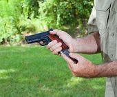 picture of pistol  - Metal magazine being inserted in a semi automatic pistol - JPG