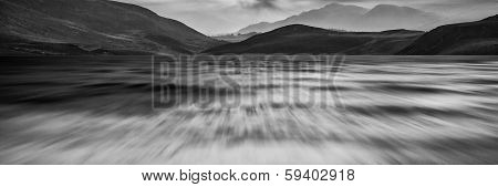 Long Exposure Panorama Landscape Of Stormy Sky And Mountains Over Lake In Black And White