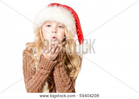 Pretty ten years girl in red Christmas cap blows off snowflakes from her hands. Isolated over white.