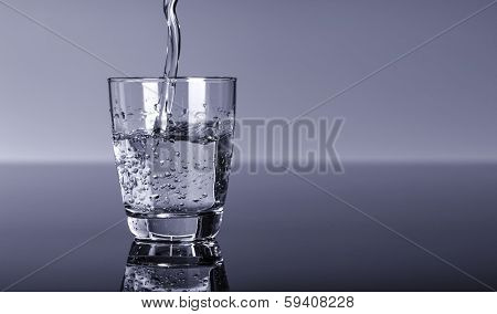 water splashing from glass on blue background, Pouring water