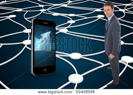 Cheerful businessman standing with hands on hips against shiny lines on black background