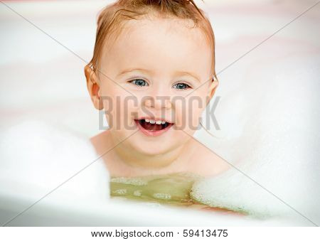 little smiling baby in a bubble bath