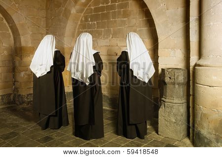 Young nuns facing the walls of a 14th century medieval abbey