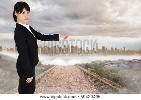 Focused businesswoman pointing against stony path leading to large urban sprawl