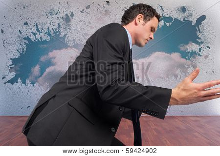 Businessman posing with arms out against splash on wall revealing bright sky