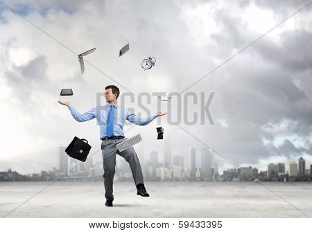 Young businessman juggling with business items against urban scene