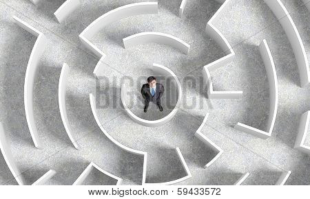 Top view of businessman standing in center of labyrinth