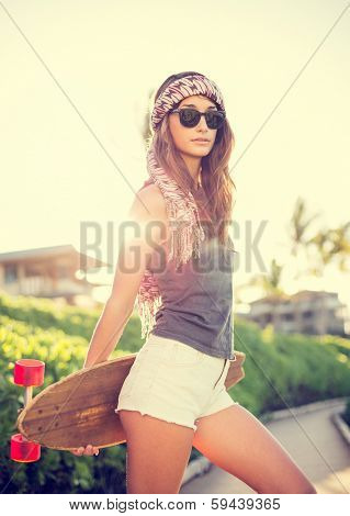 Beautiful hipster girl with skateboard, backlit at sunset