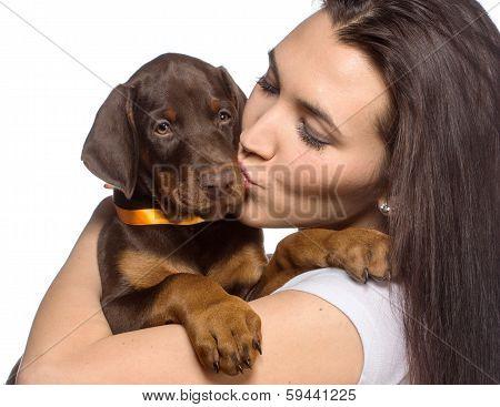 Brunette girl kissing her doberman puppy isolated on white background
