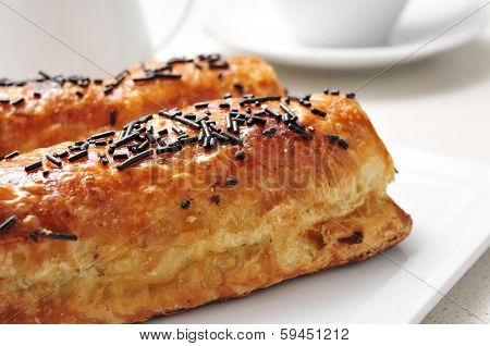 some pain au chocolat in a plate on a set table with a cup of coffee in the background