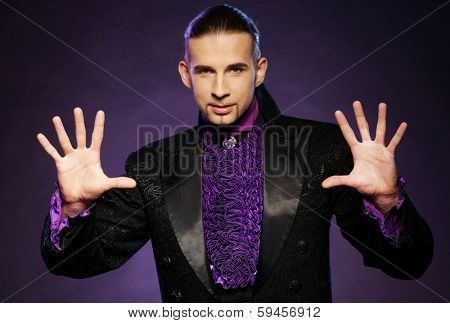 Young handsome brunette magician in stage costume