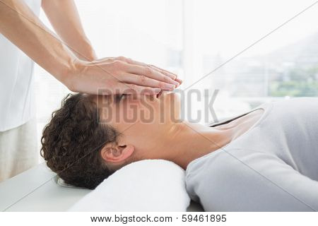 Attractive young woman having reiki treatment over face in health spa