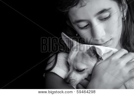 Emotional black and white portrait of a sad lonely girl hugging her small dog
