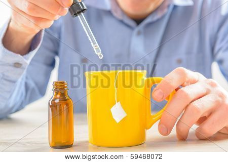 Sweetener fluid and hand with pipette whit cup of tea
