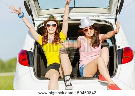 Young happy young woman sitting in car trunk outdoor