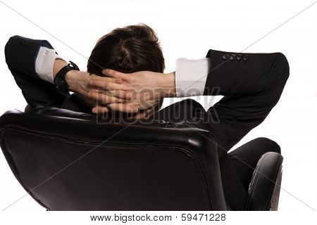 Rear view of a young Caucasian relaxed businessman sitting in a comfortable leather office chair, with the hands clasped behind his head, on white background