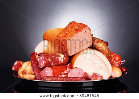 Lot of different sausages on salver on grey background