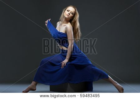 Languid nude girl posing with cloth in studio