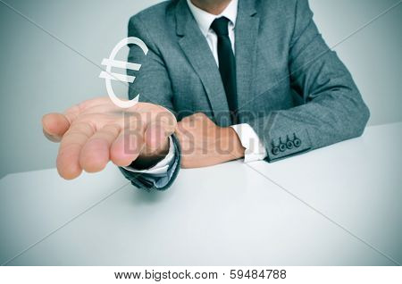 a businessman sitting in a desk showing a euro sign in his hand