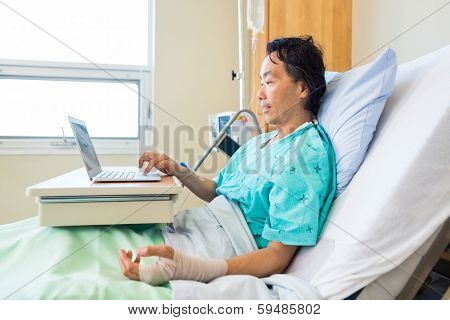 Side view of mature male patient with crepe bandage on hand using laptop on bed in hospital