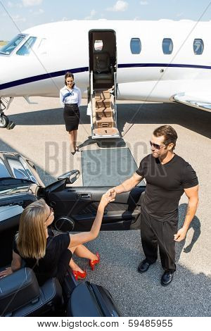 High angle view of bodyguard assisting elegant woman stepping out of car at airport terminal