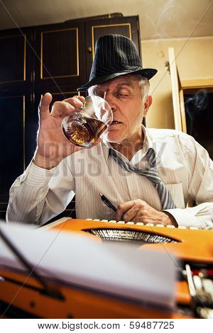 Retro Senior Man writer with a glass of whiskey