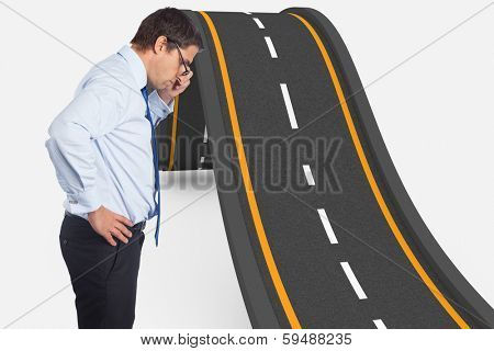 Thinking businessman tilting glasses against bumpy road background