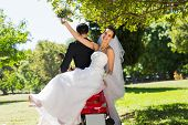 picture of scooter  - Full length of a newlywed couple sitting on scooter in the park - JPG