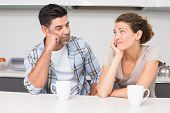 Fed up couple having coffee looking at each other at home in kitchen
