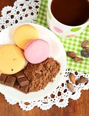 Cocoa in cup with sweets and cocoa powder on plate on wooden table