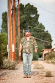 foto of dirt road  - Rugged man in camoflauge walking on dirt road - JPG