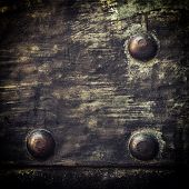foto of stelles  - Closeup of grunge black metal plate with rivets and screws as background or texture - JPG