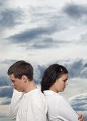 Young couple quarreling against a dramatic sky
