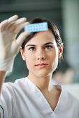 picture of microscope slide  - Young female scientist analyzing microscope slide in laboratory - JPG