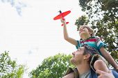 stock photo of aeroplan  - Low angle view of a boy with toy aeroplane sitting on father - JPG