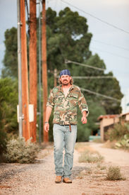 picture of dirt road  - Rugged man in camoflauge walking on dirt road - JPG