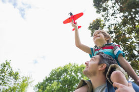 picture of aeroplan  - Low angle view of a boy with toy aeroplane sitting on father - JPG