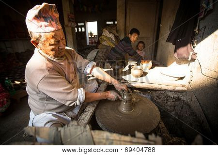 BHAKTAOUR, NEPAL - DEC 7: Unidentified Nepalese man working in the his pottery workshop, Dec 7, 2013 in Bhaktapur, Nepal. 100 cultural groups have created an image Bhaktapur as Capital of Nepal Arts.
