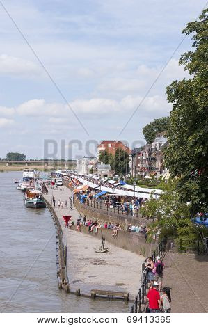 Long stripe of book stalls crowded with people along the riverside