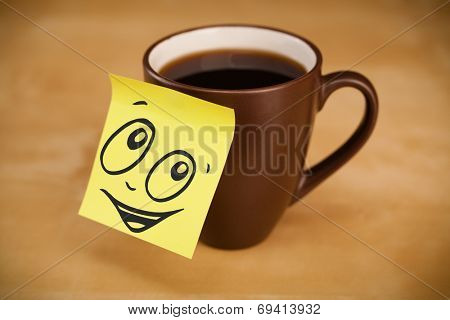 Drawn smiley face on a post-it note sticked on a cup