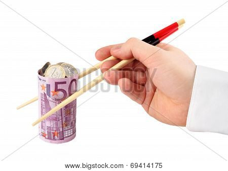Concept - lending. Banknote. Hand takes euro banknote in the form of sushi stuffed with coins on whi