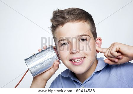 Smiling boy using a can as telephone against gray background