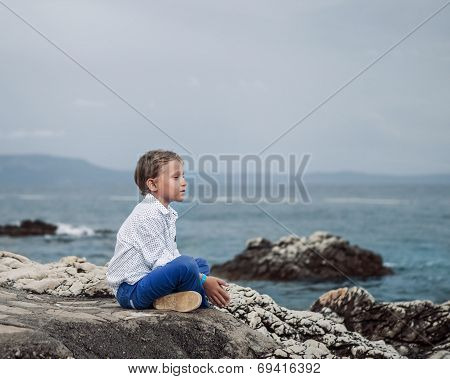 Little boy sitting calm on the solitade sea beach