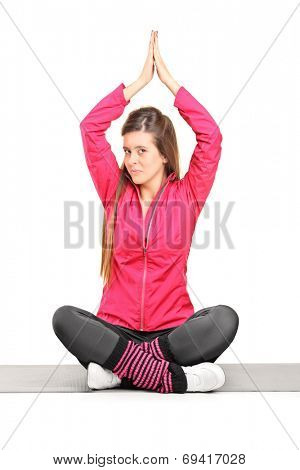 Young girl practicing yoga on the floor isolated on white background