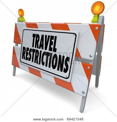 Travel Restrictions words on a road construction barrier, barricade or sign warning and blocking you from danger or harm